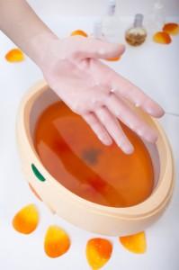 Female hand orange parrafin wax in bowl. Manicure beauty spa salon